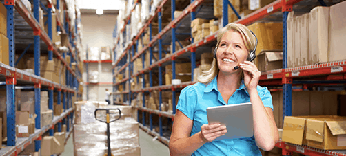 woman on warehouse floor surrounded by racking